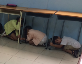 Picture of students under desks